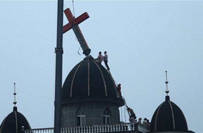 Picture from YouTube of cross being reomved from a Chinese church